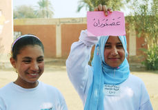 Two Happy Muslim girls holding arabic word. (translation two birds)  on colored cardboard Muslim girls posing smiling for the camera wearing and they are shy Royalty Free Stock Image