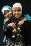 Two Happy Muslim Girls with Ramadan Lantern. On Black Background