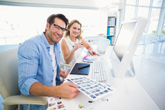 Two happy photo editors working with contact sheets Royalty Free Stock Photography
