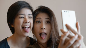 Two happy photogenic Asian womans talking selfie with phone Royalty Free Stock Images