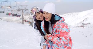 Two happy playful young ladies at a ski resort. Standing grinning at the camera in a snow inter landscape with copy space stock video footage
