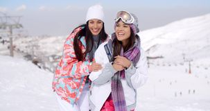 Two happy playful young ladies at a ski resort. Standing grinning at the camera in a snow inter landscape with copy space stock video