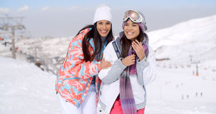 Two happy playful young ladies at a ski resort Stock Photo