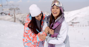 Two happy playful young ladies at a ski resort Royalty Free Stock Photo