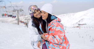 Two happy playful young ladies at a ski resort Royalty Free Stock Image