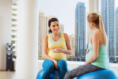 Two happy pregnant women sitting on balls in gym Royalty Free Stock Photos