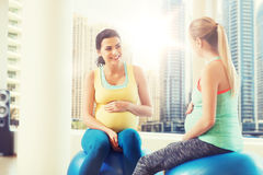 Two happy pregnant women sitting on balls in gym Stock Images