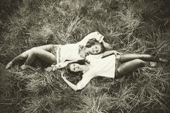 Two happy pretty girls lying on the grass Royalty Free Stock Images