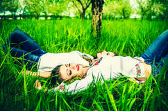 Two happy pretty girls lying on the green grass Royalty Free Stock Photo