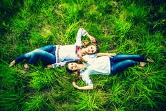Two happy pretty girls lying on the green grass Stock Images