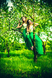 Two happy pretty girls sitting on the blossom apple tree Royalty Free Stock Images