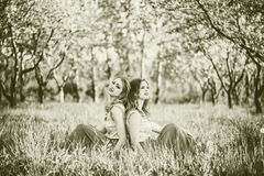 Two happy pretty girls sitting on the blossom apple tree Stock Photos