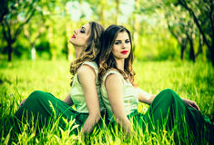 Two happy pretty girls sitting on the green grass Royalty Free Stock Photography