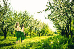 Two happy pretty girls walking on the apple trees garden Stock Photo