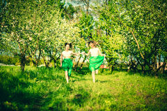 Two happy pretty girls walking on the apple trees garden Royalty Free Stock Image