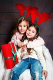 Two happy little smiling girls with christmas gift boxs on wooden background. Merry christmas and happy new year . Two happy pretty little smiling girls with Stock Photography