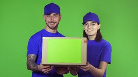 Two happy professional delivery workers holding out package box to the camera stock video footage