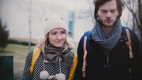Two happy relaxed Caucasian friends, young man and woman, walking, talking and smiling in the street on cold winter day. stock video