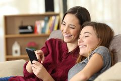 Two happy roommates checking smart phone content at home royalty free stock images