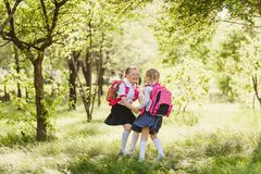 Two happy school girls of primary classes outdoors stock photos