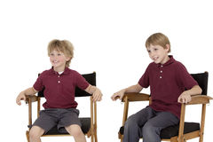 Two happy school kids sitting on director's chair over white background Stock Image