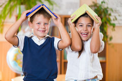 Two happy schoolchildren have fun in classroom Stock Images