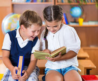Two happy schoolchildren have fun in classroom Royalty Free Stock Photography