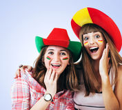 Two happy screaming girls - football fans. Two happy screaming girls football fans in bright hats Royalty Free Stock Photo