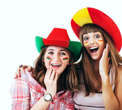 Two happy screaming girls - football fans. Two happy screaming girls football fans in bright hats Royalty Free Stock Images