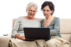 Two happy senior and adult women with a laptop Royalty Free Stock Photos