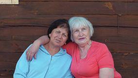 Two happy senior women hugging and singing together near wooden wall
