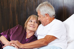 Two happy seniors in bed. Two happy seniors laying together in a bed stock image