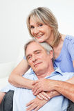 Two happy seniors embracing each. Other at home on couch Stock Photos