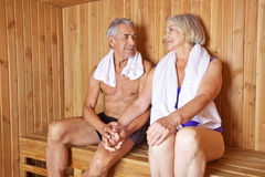 Two happy seniors holding hands. Two happy seniors holding their hands in a sauna in a hotel stock photo