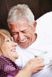 Two happy seniors laughing in bed. Two happy seniors laughing together in a bed royalty free stock photography
