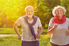 Two happy seniors running in nature. Two active happy seniors running in nature in summer stock images