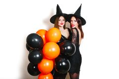 Two happy sexy women in black witch halloween costumes with orange and black balloon on party over white background Royalty Free Stock Image