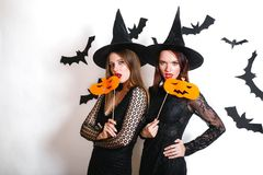 Two happy women in black witch halloween costumes with pumpkin on party over white background Royalty Free Stock Images