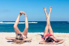 Two happy sexy women friends sunbathing on the tropical beach of Bali island, Nusa Dua, Indonesia. Royalty Free Stock Photos