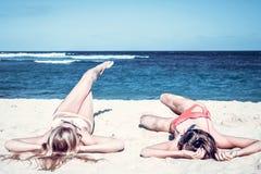 Two happy women friends sunbathing on the tropical beach of Bali island, Nusa Dua, Indonesia. Royalty Free Stock Image