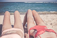 Two happy women friends sunbathing on the tropical beach of Bali island, Nusa Dua, Indonesia. Royalty Free Stock Images
