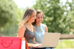 Two shoppers searching products on a laptop. Two happy shoppers searching products on a laptop in a park stock photo