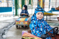 Two happy sibling boys in blue jackets and rain boots playing with big old toy car, outdoors. Kids leisure on cold day in winter, royalty free stock images