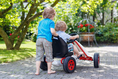 Two happy sibling boys having fun with toy car Stock Images