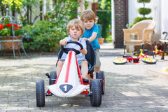 Two happy sibling boys having fun with toy car Royalty Free Stock Photography