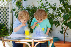 Two happy sibling boys making experiment with colorful bubbles. Two happy sibling boys making experiment with colorful soap bubbles and water, outdoors stock photos