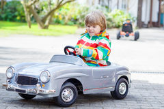 Two happy sibling boys playing with big old toy car Royalty Free Stock Photo