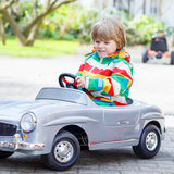 Two happy sibling boys playing with big old toy car Stock Photos