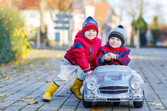 Two happy sibling boys playing with big old toy car, outdoors Stock Image