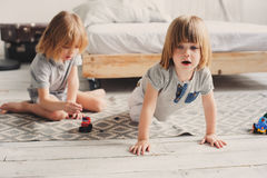 Two happy sibling boys playing together at home with toy cars Stock Image
